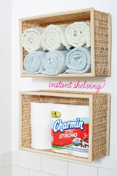 Woven baskets used as towel shelves against the wall