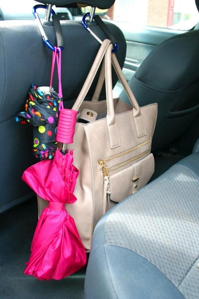 Handbag and umbrellas hanging from a car headrest
