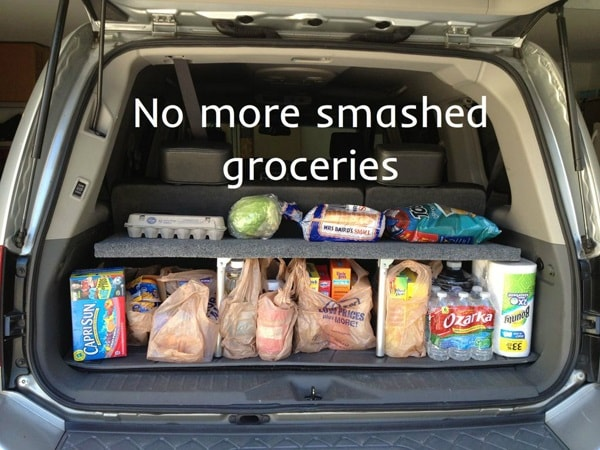 A fold-able shelf filled with groceries inside the trunk of a car