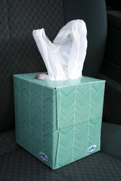 A blue tissue box filled with plastic bags
